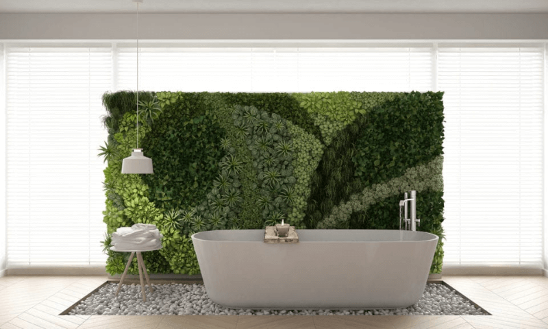 A white bath next to the green wall with artwork display.