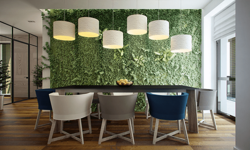Green wall with a dining table set and white lamps hanging like dancing musical notes.