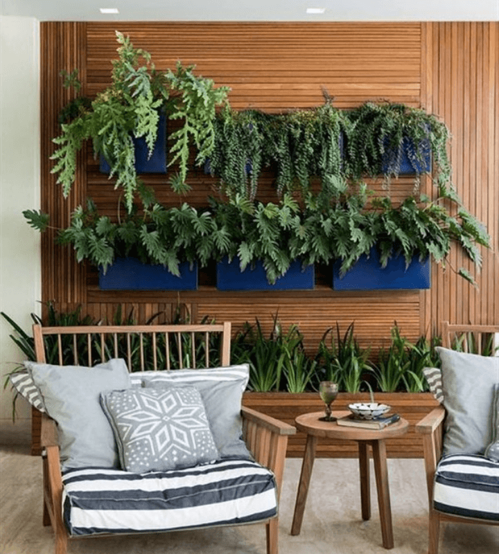 Blue wall-mounted planters with lush foliage plants and a sleek rectangular wooden raised bed of air purifying plants.